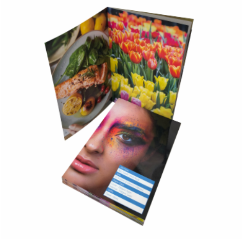 There is a stack of colourful saddle stitched books. There is a portrait of a woman with bright make-up on the cover. One of the books is open to images of a delicious salmon dish and a field of tulips.