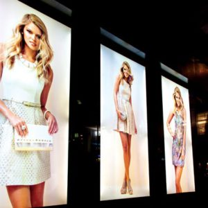 Three glowing lightbox skins light up a shop front. A model in fashionable clothes is on each one.