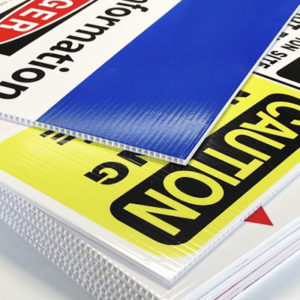 A stack of our high quality white corflute signs. There are caution and danger graphics printed on the surface.
